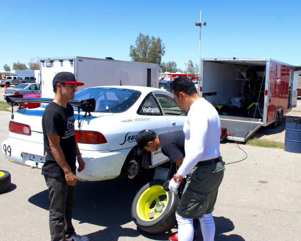 Hartanto and Boisdeau discuss while James Tam inspects the Integra's brakes and tires